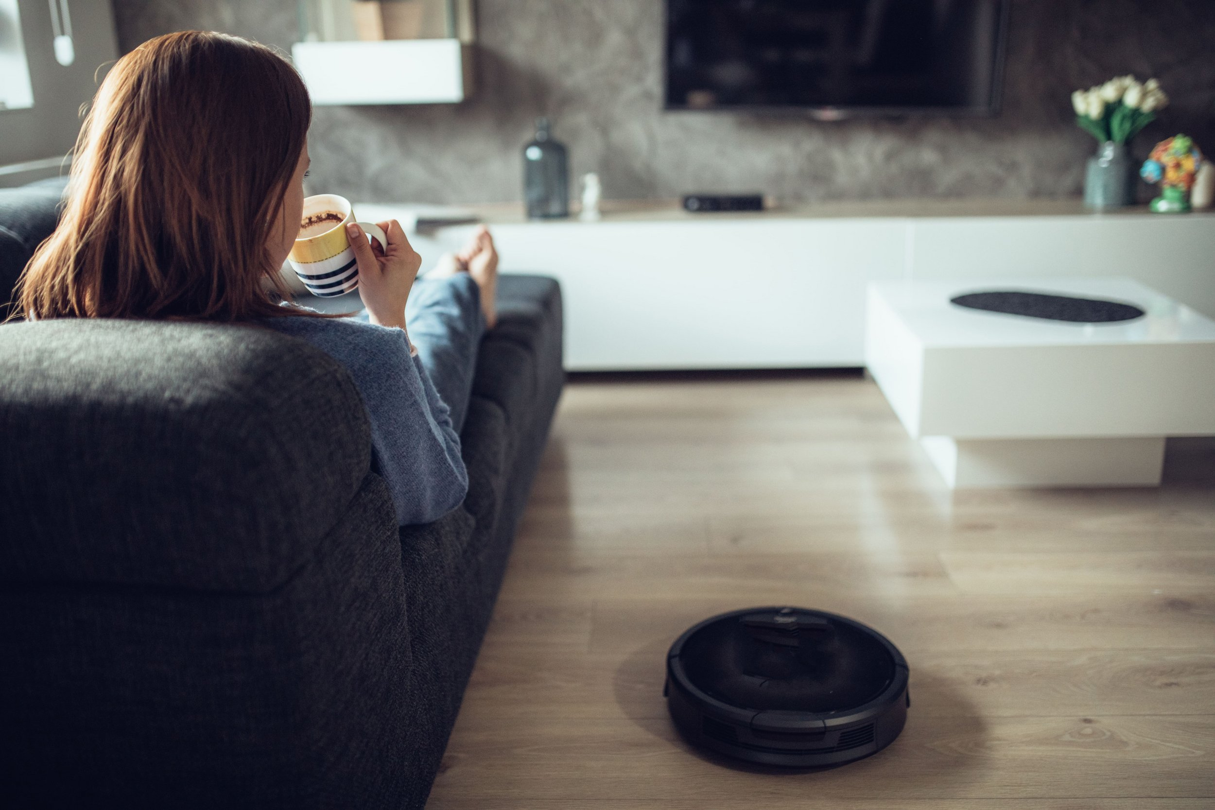 Woman relaxing on sofa next to vacuum cleaner robot